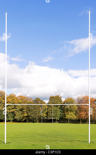 Rugby posts on green field with trees and blue sky - Stock Image