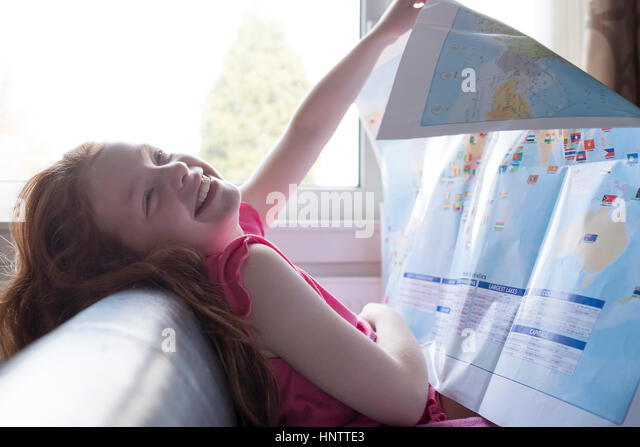 A little girl looking at a map in her bedroom - Stock Image