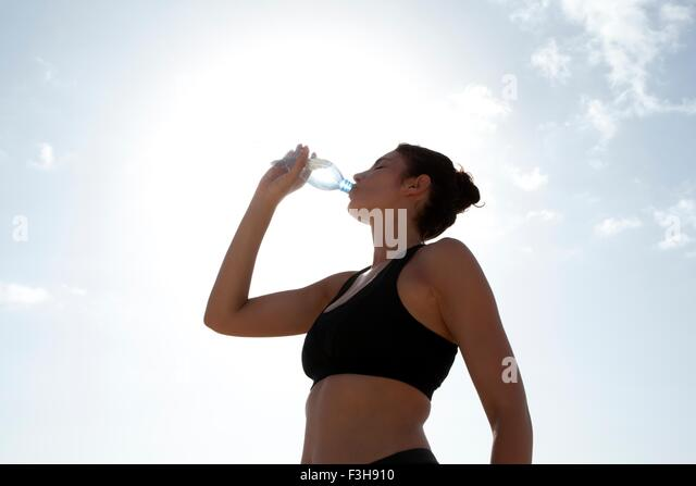 Low angle view of blue sky and mid adult woman drinking bottled water - Stock Image