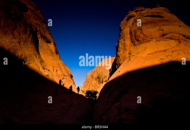 Three people hike through Coyote Wash as the sun sets in Grand Staircase-Escalante National Monument in Utah. - Stock Image
