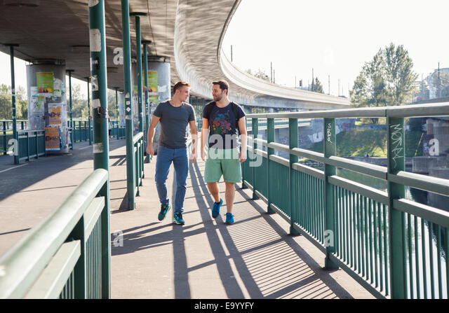 Two young men chatting as they walk over bridge - Stock Image