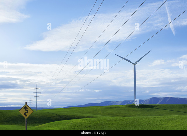 Wind turbines on a grassy hilltop road sign warning Winding Road Green sustainable energy production Washington - Stock Image
