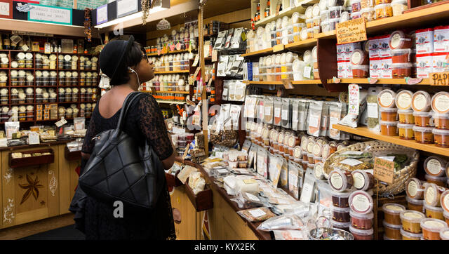 Customer browsing spices on sale at the Spice Mountain shop at Borough Market, London, England, United Kingdom - Stock Image