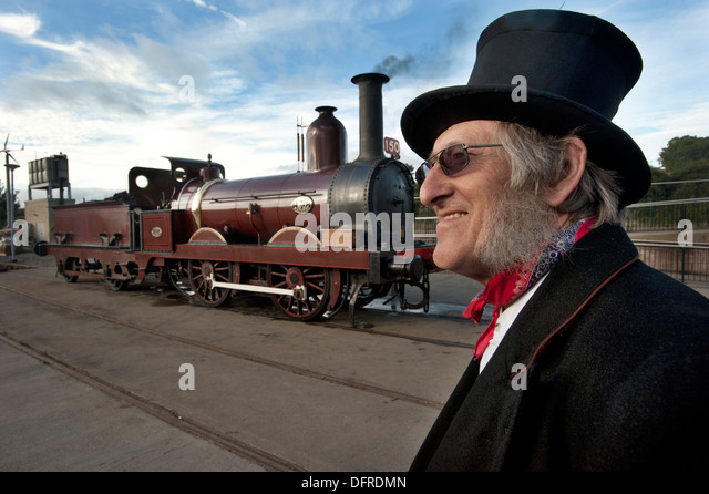 A Period dressed driver Alan Middleton wearing a Top Hat by his steam locomotive Furness Railway number 20, Britains - Stock Image
