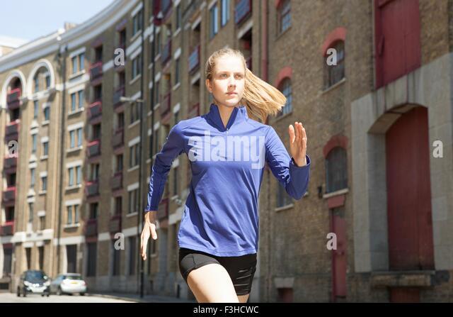 Runner jogging past building block, Wapping, London - Stock-Bilder