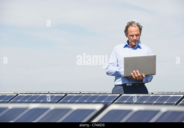 Germany, Munich, Mature man using laptop in solar plant - Stock Image