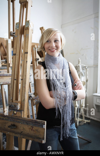 Female student standing among easels in art college - Stock Image
