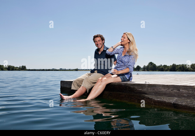 Couple relaxing together on dock - Stock Image