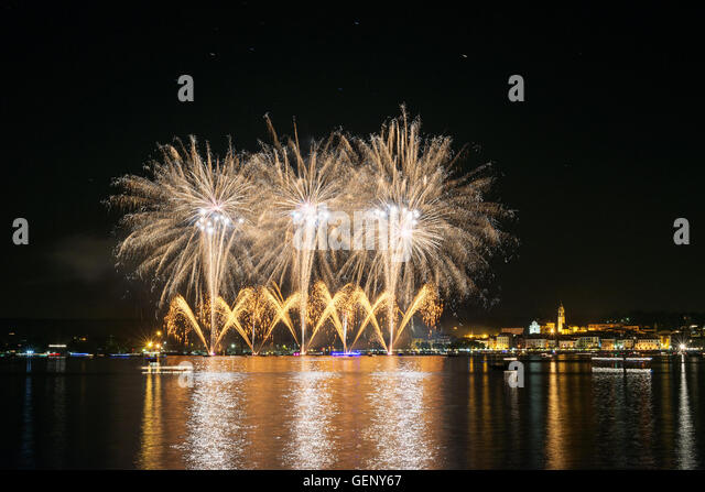 Fireworks on the lakefront of Arona in a summer party night seen from Angera, Major Lake- Piedmont - Stock Image
