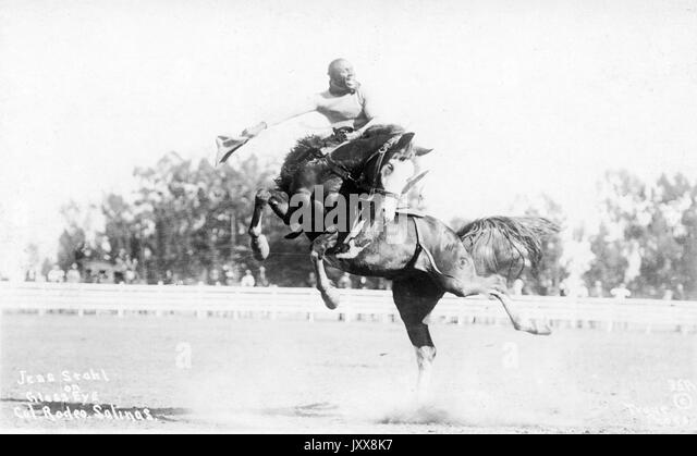 African American cowboy Jess Stahl smiles as he rides horse Glass Eye in the area at the California Rodeo Salinas, - Stock Image
