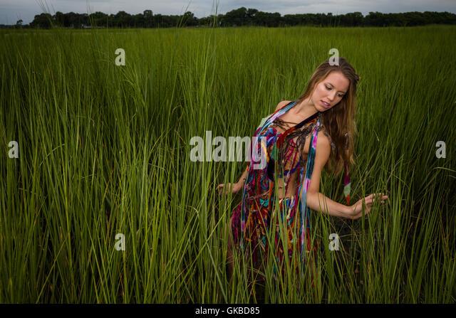 Young woman in tall green grass, Virginia Beach, VA - Stock Image