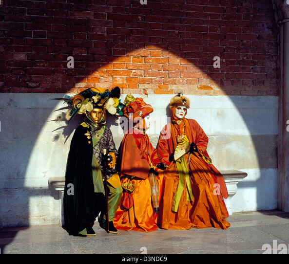 Three masks dressed up in historical costumes sit on a bench at St Mark's Basilica (Basilika di San Marco), - Stock Image
