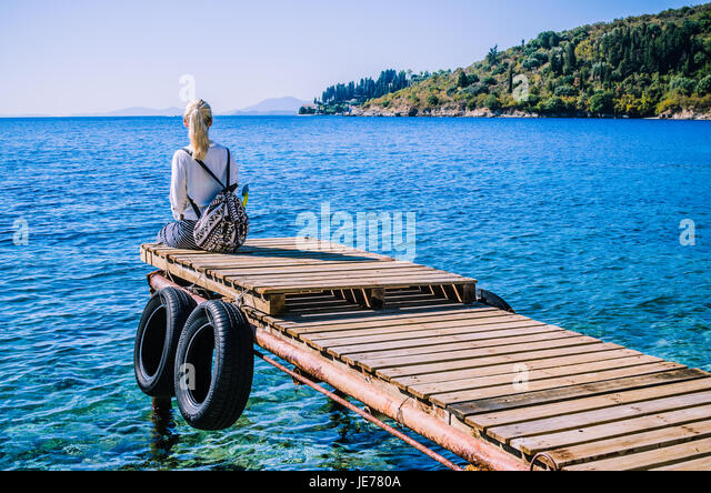 Girl with backpack on pier on the beach near Kalami looking into sea. Corfu Island, Greece - Stock Image