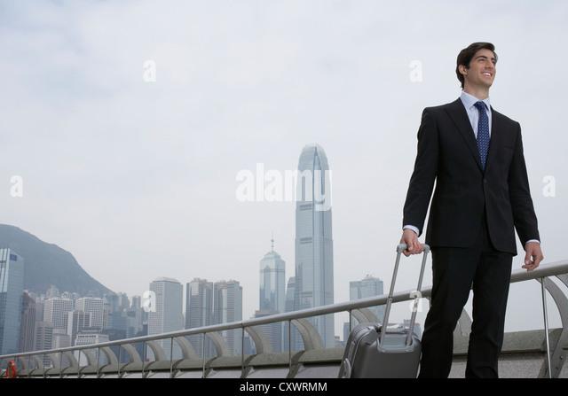 Businessman with luggage by urban bay - Stock-Bilder