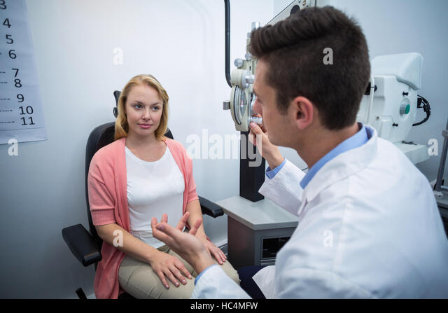 Optometrist assisting female patient - Stock Image