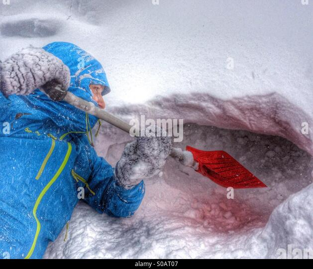 Digging a snow shelter to hide for a snow storm. - Stock Image