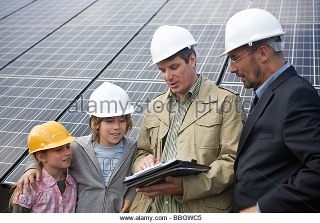 Mature businessmen teaching children about solar energy, Munich, Germany - Stock Image