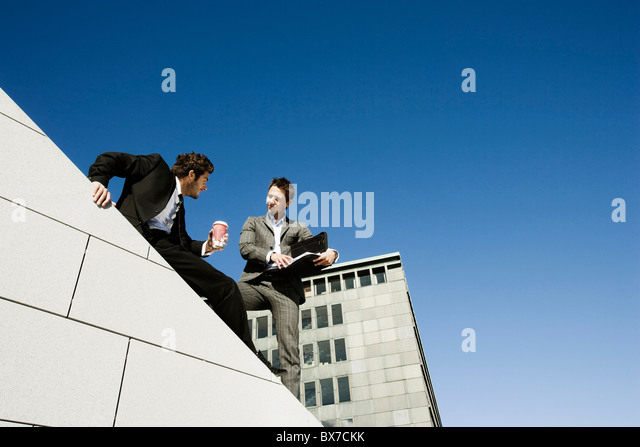 Men doing business on roof - Stock Image