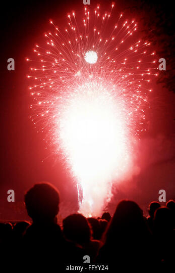 Crowd Looking At Firework Display During New Years Eve - Stock Image