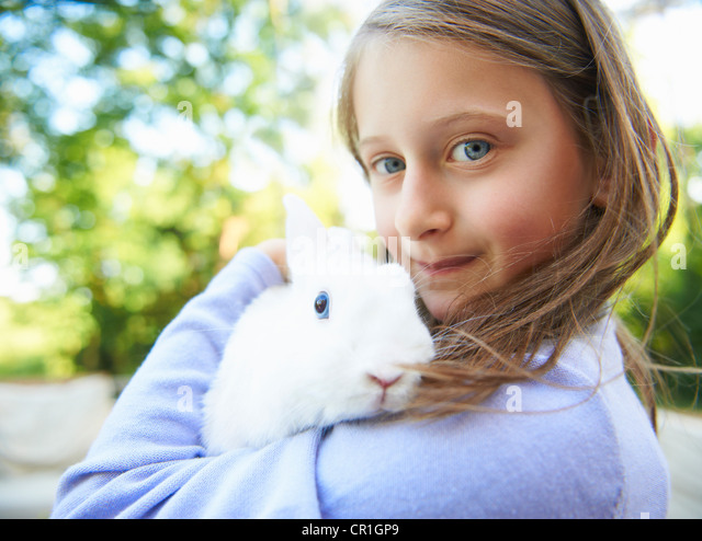 Close up of girl holding pet rabbit - Stock Image
