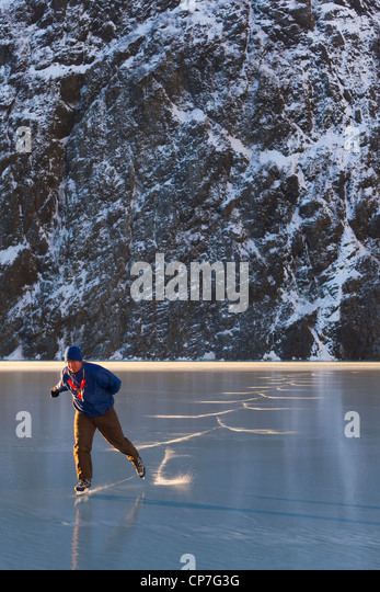Man ice skating in front of Saddlebag Glacier, Chugach Mountains near Cordova, Southcentral Alaska, Winter - Stock Image