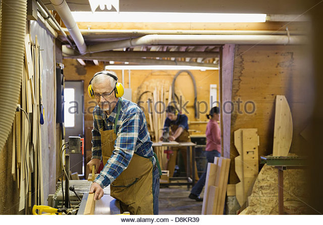 Senior carpenter using equipment in workshop - Stock Image
