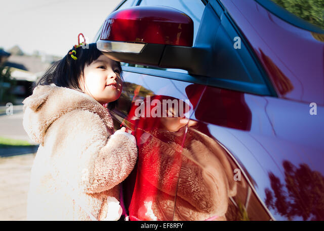 Australia, Melbourne, Young girl looking in side-view mirror - Stock Image