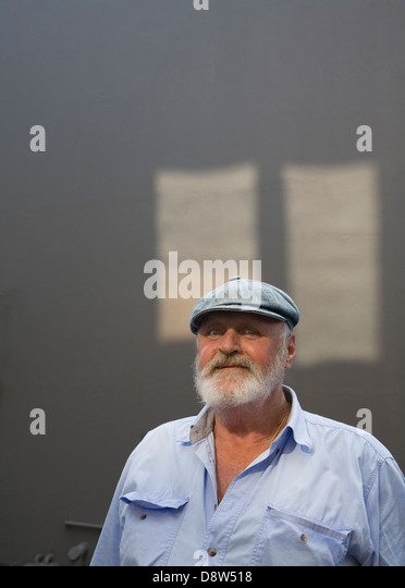 Man 50s, with grey beard, wearing cloth cap and blue shirt, against grey wall with patches of sunlight, staring - Stock Image