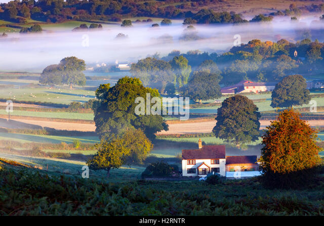 A cottage in the rural village of Rhes-y-Cae is surrounded by morning mist as an inversion takes hold in the area, - Stock Image
