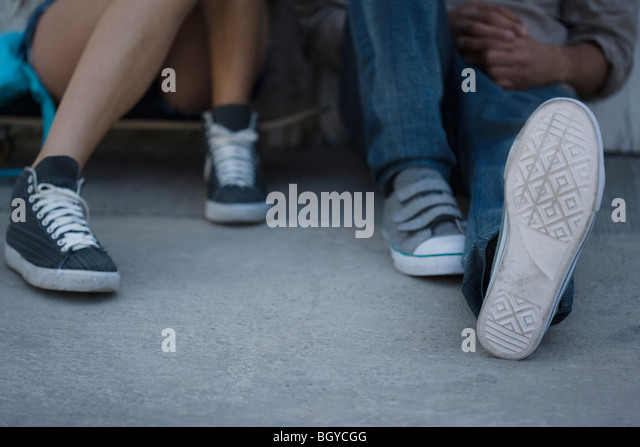 Young people sitting side by side hanging out, low section - Stock Image