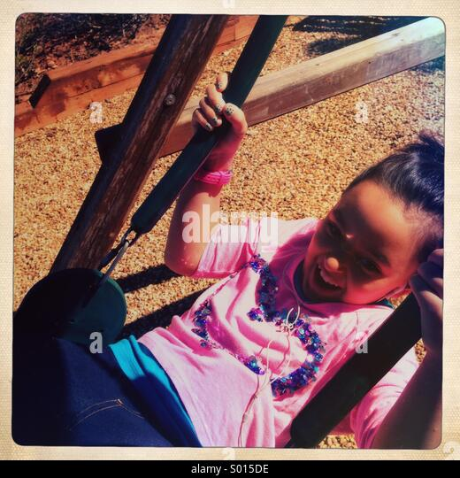 Little girl laughing on swing - Stock-Bilder