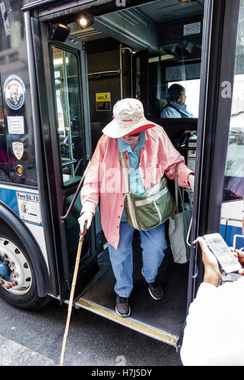 Manhattan New York City NYC NY Midtown MTA bus public transportation stop woman senior cane exiting getting - Stock Image