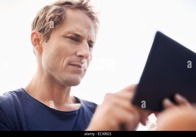 Mature man using tablet computer against clear sky - Stock Image