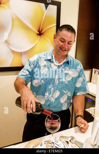 Hawaii Hawaiian Honolulu Waikiki Beach Hilton hotel concierge lounge man host pouring wine bottle glass bartender - Stock Image