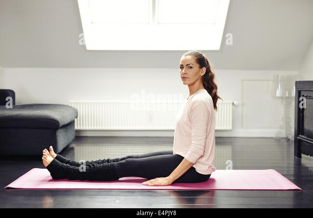 Portrait of fit young woman sitting on exercise mat looking at camera. Healthy female exercising at home. - Stock Image