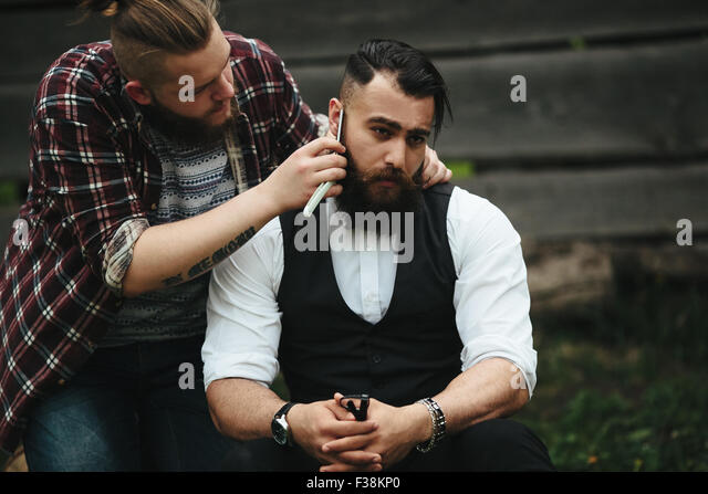barber shaves a bearded man - Stock-Bilder