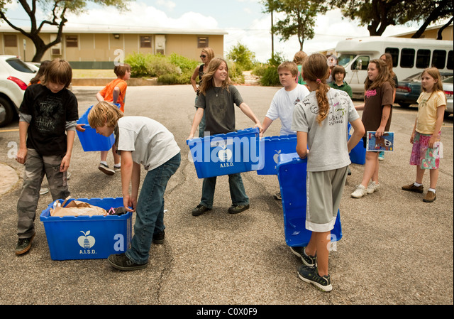Fifth-grade elementary students carry papers to recycle dumpster at school as they clean classrooms at end of the - Stock Image