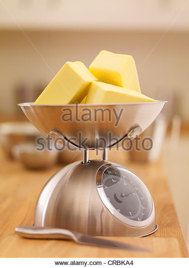 Cubes of butter on scale - Stock Image