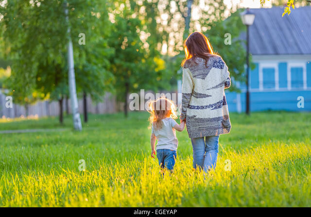 Mother and little daughter walking in sunny park - Stock Image