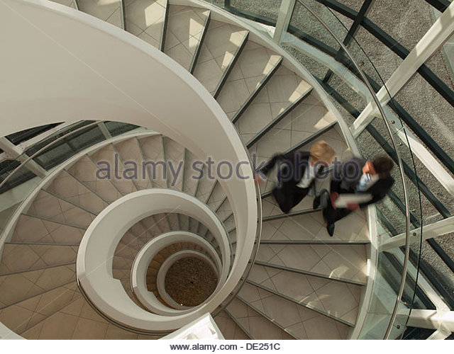 Business people descending circular staircase - Stock-Bilder
