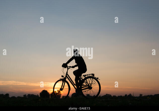Germany, North Rhine-Westphalia, Cycling at sunset along Rhein River - Stock Image