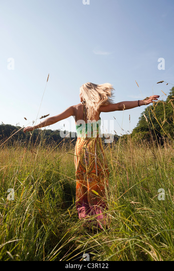 Germany, Dortmund, Young woman turning and having fun - Stock Image