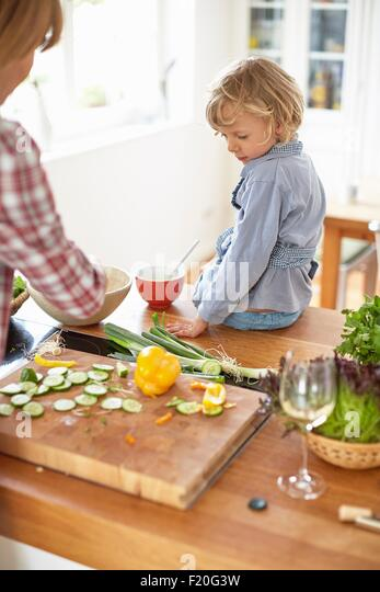 Mother and son preparing meal in kitchen - Stock Image