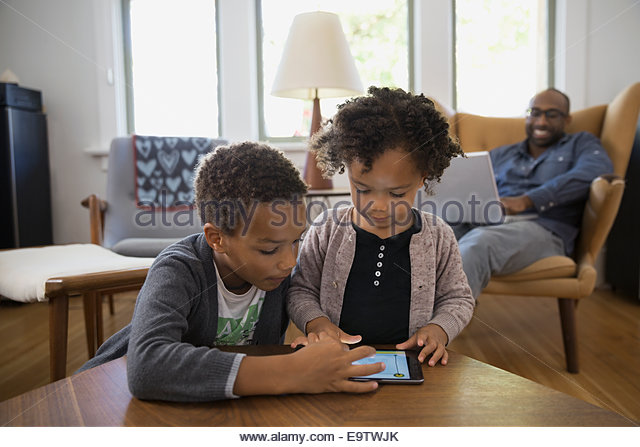 Brother and sister sharing digital tablet - Stock Image