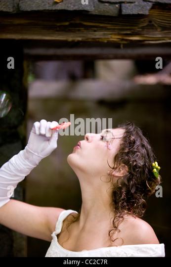 Bride blowing bubbles - Stock Image
