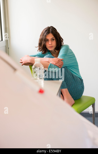Female depressed patient sitting on the chair in a hospital ward - Stock Image