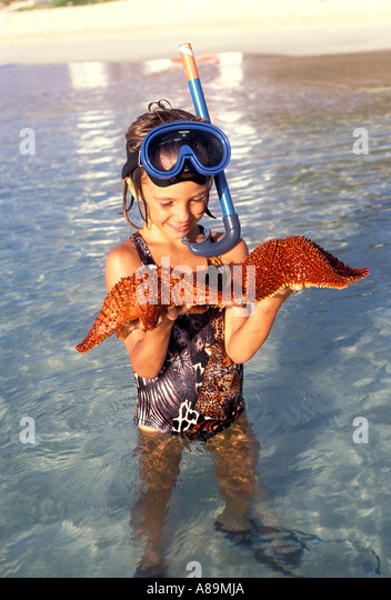 Anguilla beach caribbean beach island young girl wearing snorkel and mask holds starfish out of water caribbean - Stock Image