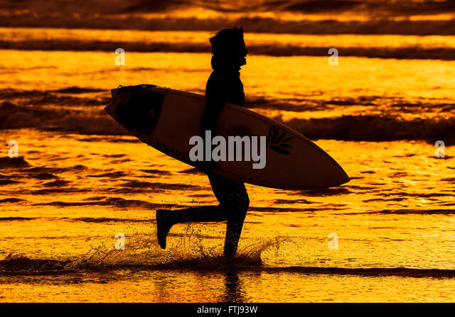 The silhouette of a surfer running along the shoreline on Fistral Beach during an intensely colourful late evening - Stock-Bilder