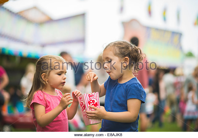 Two young sisters sharing popcorn at funfair - Stock Image