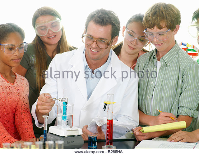 Teacher helping students (12-14) with chemistry experiment - Stock Image